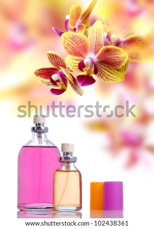 Perfume in bottle on yellow orchid background