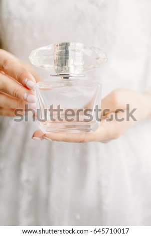 Perfume in female hands, the bride in a white dress holds a bottle of perfume, a glass bottle in her hands, a light manicure, a manicure for the bride, wedding details close-up. - Shutterstock ID 645710017