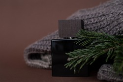 Perfume, Men's perfume or lation After shave on a brown background next to a men's sweater and Needles, Spruce. Luxury, Gift. Close-up Photo for advertising a perfume shop, blog