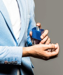 Perfume or cologne bottle. Male fragrance and perfumery, cosmetics. Man perfume, fragrance. Masculine perfume. Man holding up bottle of perfume.