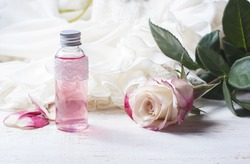 perfumed rose water in a bottle on a wooden table.  Selective focus