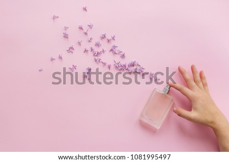 perfumery and floral scent concept. hand holding stylish bottle of perfume with spray of lilac flowers on pink background. creative trendy flat lay with space for text. modern image #1081995497