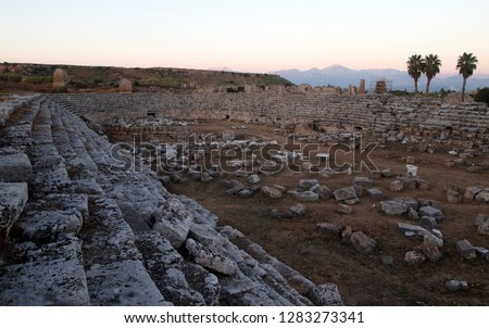 Perge Stadium (ancient city near Antalya, Turkey) ruins at sunset. Seating stands, most of the stadium, mountains and palm trees in the background, beautiful colors. No people. #1283273341