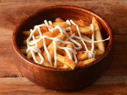 Peri Peri French Fries, topped with mayonnaise, served in a wooden bowl over a rustic wooden background, indian cusine, selective focus