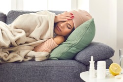 Period of seasonal diseases. Close up of a sick woman with flu, fever and headache lying wrapped in a plaid on the couch. Woman with closed eyes touches her hot forehead. Concept of viral diseases.