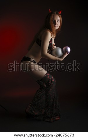 Perky young woman stealing christmas balls in the dark, stage costume of devil