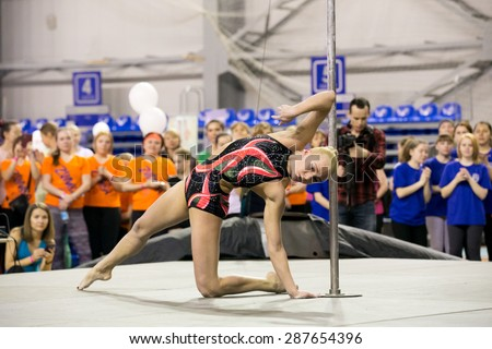 Perm, Russia - April 25, 2015. Championship Perm region at pole sport and dance.  blonde in a black swimsuit with a pink pattern dance near pole