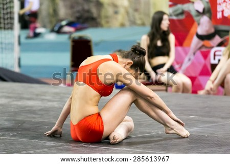Perm, Russia - April 25, 2015. Championship Perm region at pole sport and dance. brunette in red dance costume sitting on the floor buried in knee