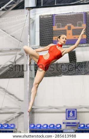 Perm, Russia - April 25, 2015. Championship Perm region at pole sport and dance. Serious brunette in a red  dance suit makes  element a hook knee