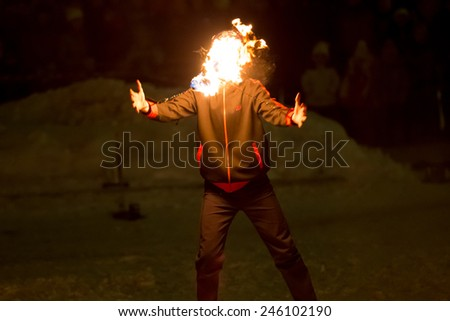 Perm, Russia - January 17, 2015. Fiery poi on circuit covered his face man