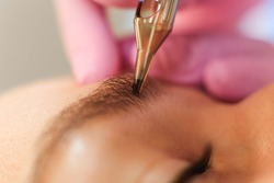 permanent  eyebrows makeup.  tattoo of eyebrows made by sterile needle with disposable gloves