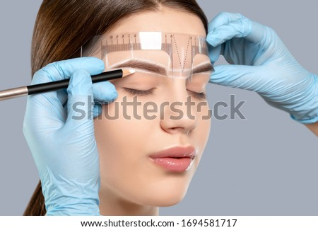 Permanent make-up for eyebrows of beautiful woman with thick brows in beauty salon. Closeup beautician doing tattooing eyebrow. Professional makeup and cosmetology skin care. Foto stock ©