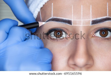 Shutterstock Permanent make-up for eyebrows of beautiful woman with thick brows in beauty salon. Closeup beautician doing  tattooing eyebrow.