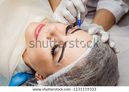 Permanent Makeup For Eyebrows. Closeup Of Beautiful Woman With Thick Brows In Beauty Salon. Beautician Doing Eyebrow Tattooing For Female Face. Beauty Procedure. High Resolution #1131119333