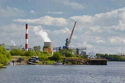Permian region, Russia - August 2017:  An old harmful plant with red-white pipes and towers on the bank of the river against the background of a cloudy sky. Industrial landscape