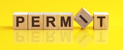 Permit word written on wood block. Permit word is made of wooden building blocks lying on the yellow table. business concept, yellow background