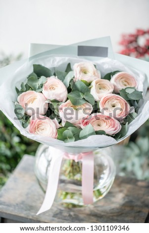 Persian buttercup in glass vases. Bunch pale pink ranunculus flowers with green eucalyptus. Beautiful fresh cut bouquet in vase on wooden table. the work of the florist at a flower shop #1301109346