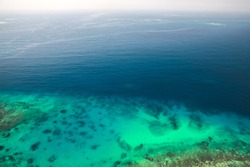 Persian Gulf seascape, rocky seabed is under blue shallow water. Natural photo. Bird eye view