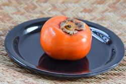 Persimmon Fruit shiney selective focus isolated on textured white background. Sharon fruit Kaki of Japan