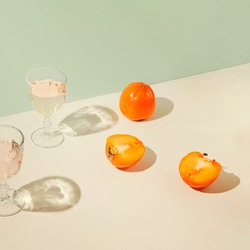 Persimmon fruits and glasses of water on geometric pastel background with sunlit. Summer drinks and refreshment concept.  Minimal style composition