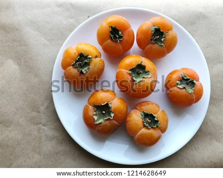 Persimmon fruits on plate. Ripe. High resolution photography.