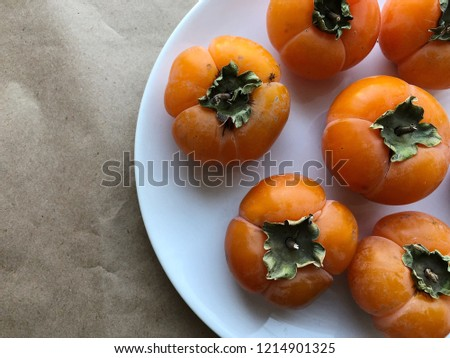 Persimmon fruits on the plate. High resolution photography.