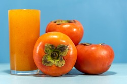 Persimmon juice and fruits on the blue background. Persimmon juice has a reserve of various phytochemicals such as catechins and polyphenolic antioxidants. Detox and refreshing drink.