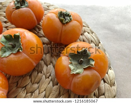 Persimmon ripe fruits on straw plate. High resolution photography.
