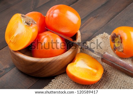 persimmons in bowl on wooden table