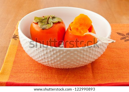 Persimmons in bowl with spoon. selective focus.