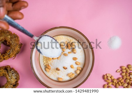 person adding sugar to a bowl of garri, with groundnut and fish