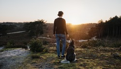 Person and dog stands thoughtfully in nature and have a wonderful view of the landscape. At sunrise they look out into the distance The woman and the husky enjoy life, are happy and content.