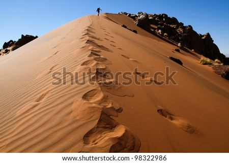 Person ascending a mountain covered with sand in the Namib desert - stock photo