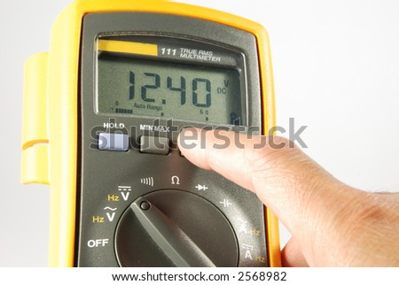 person changing settings on fluke digital meter. checking vehicle battery voltage
