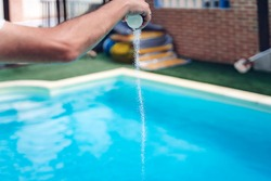 Person cleaning and chlorinating the pool on a hot summer afternoon, is running the cleaner and adding chlorine powder