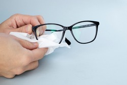 Person Cleaning Black Eyeglasses  With Special Wipes