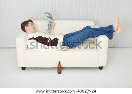 Person comfortably lie on a sofa with a beer and journal