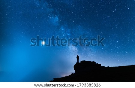 Person contemplating the vastness of the universe. Small silhouette of a man under the Milky Way and the magical starry sky. Concept of human smallness. Foto stock ©