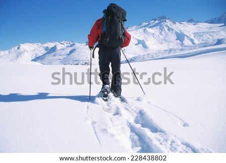 Person crossing snow-covered landscape in snowshoes