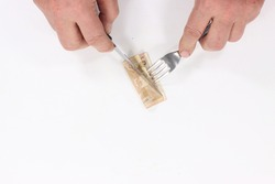 person cutting fifty euro currency banknote