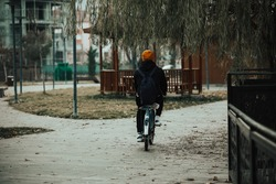 Person cycling in the park. Young boy goes to school by bike. Boy cycling for a healthy lifestyle. 2021 is the year of healthy living.