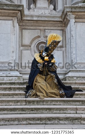 Person disguised in extravagant colorful dress with mask sitting on the stairs during the famous Carnival in Venice, Italy. The traditional festival is well known mainly for ist beautiful masks.  #1231775365