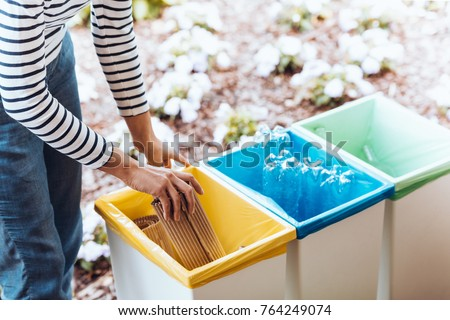 Person disposing of paper, throwing it into a yellow bin on terrace