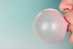 Person doing bubble with chewing gum on bright background