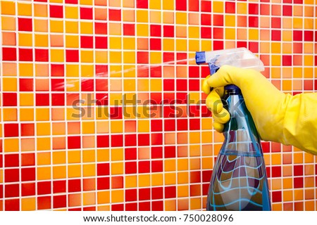 Person doing chores in bathroom at home cleaning red orange tiled wall with spray detergent