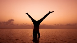 Person doing yoga pose at sunset. Yoga silhouette on sunrise. Yoga concept. Healthy lifestyle concept. Person doing headstanding while the sunset. Unity with nature. Meditation on sunset.