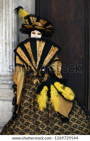 Person dressed in Venice mask wearing black and gold Venetian costume holding a fan at the Venice Carnival in Italy #1269729544