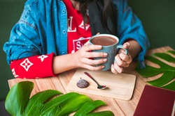 Person drinking hot chocolate in a coffee shop - leaves and decoration in a cafe - coffee shop hot chocolate