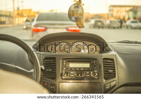 Person driving a car at sunset evening sky light Autumn Road between houses control Focus on arrow speedometer and tachometer audio system Empty copy space for inscription