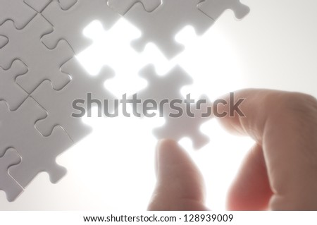 Person fitting puzzle pieces against the light.Soft focus photograph. Concept image of building.